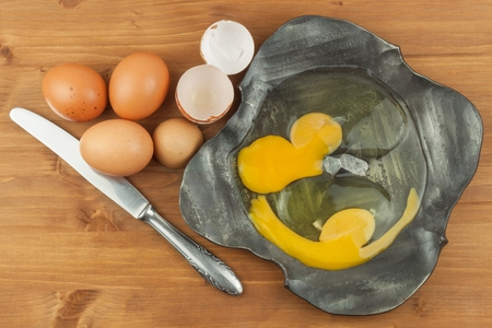 protein source: Broken eggs on forged metal bowl. Domestic eggs on a wooden table. Source of quality protein. Metal bowl of raw eggs and egg shells.