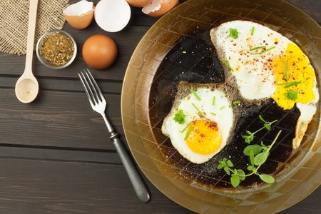 dietary supplements: Fried fried egg on steel pan. Preparing homemade dietary supplements. Pan on a dark wooden table. Fried eggs.