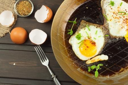 steel pan: Fried fried egg on steel pan. Preparing homemade dietary supplements. Pan on a dark wooden table. Fried eggs.