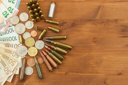 Grocery ammunition, weapons and ammunition sales. Valid euro banknotes and coins. Different types of ammunition. Preparing for war. Stock Photo