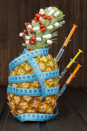 dietary supplements: Diet food. Ripe pineapple and measuring tape on a wooden background. Pills and dietary supplements. For you.