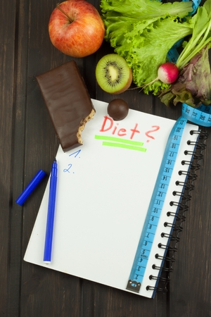 initiate: Preparing for the diet program. The decision to initiate dieting. Planning of diet. Notebook measuring tapes and pen on wooden table.