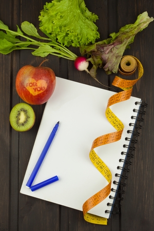 weightloss plan: Preparing for the diet program. The decision to initiate dieting. Planning of diet. Notebook measuring tapes and pen on wooden table.