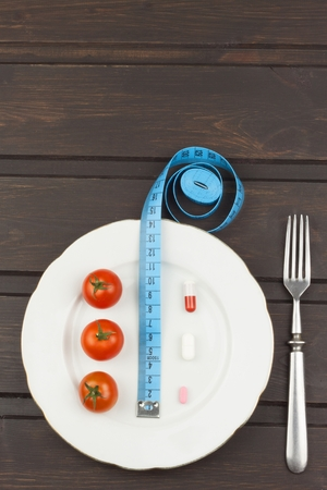 strict: Diet and supplements on a wooden table. Strict diet meals. Slimming diet. Tomatoes and pills.