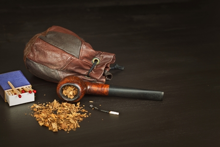 Old tobacco pipe and spilled tobacco, used on a black wooden background. Shabby old tobacco pipe. Wooden tobacco pipe on a black background. Relaxing with a tobacco pipe. Quiet place. Chain smoker. Stock Photo