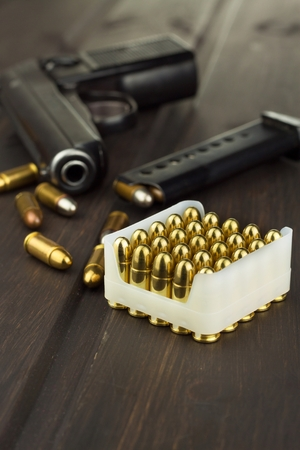 luger: Handgun with ammunition on a dark wooden table. Sales of weapons and ammunition. Advertising on ammunition. New gun and ammunition. Grocery ammunition. The supply of ammunition for the defense.