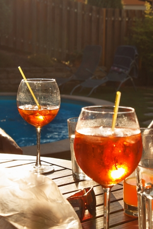 refreshments: Cold summer drink by the pool. Party with refreshments by the pool. Alcohol drink with ice. Glasses with a refreshing drink. Alcohol at the party.