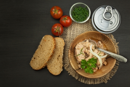 Crushed canned tuna. The fishing industry, canned fish. Diet food. Tinned tuna. Bowl with canned Tuna. Domestic food preparation.