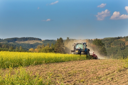 previously: Blue tractor in a field of mustard in the Czech Republic. Dusty field and agricultural work. Autumn farm chores. The tractor mows mustard on a sunny day. Farmer working in the field.