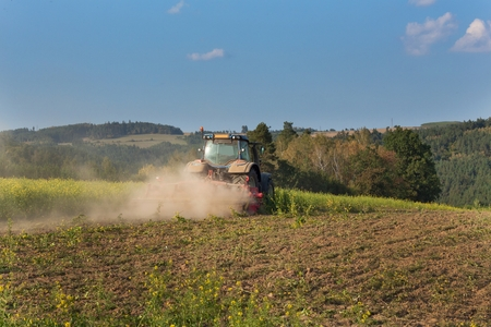 mows: Blue tractor in a field of mustard in the Czech Republic. Dusty field and agricultural work. Autumn farm chores. The tractor mows mustard on a sunny day. Farmer working in the field.