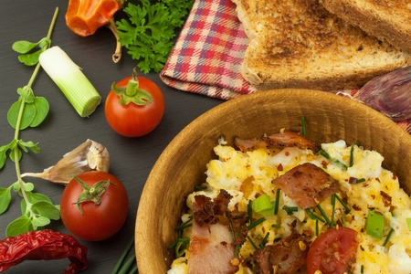 cebollines: Scrambled eggs with fried bacon. English breakfast. Toast and scrambled eggs with chives. Recipe for a healthy meal.