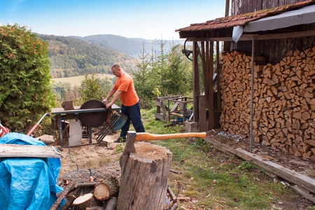 Man cuts wood. Man cutting firewood, preparing for winter. Firewood for heating. Stock Photo