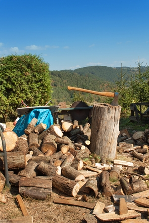 Old ax on log and firewood. Axe Cut into Wood after Chopping Firewood.