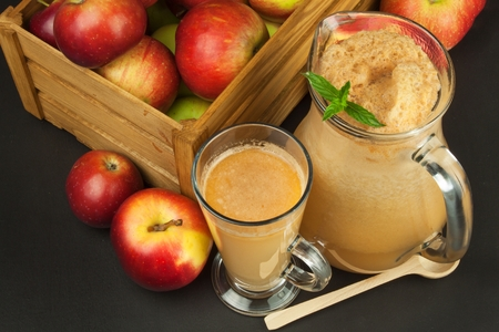 unfiltered: Fresh pressed apple juice unfiltered. Apple juice and apples on wooden table. A healthy juice for athletes. Autumn apple harvest.