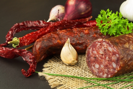 Dried sausages on wood. Homemade rustic sausages and chili. Sharp traditional food.