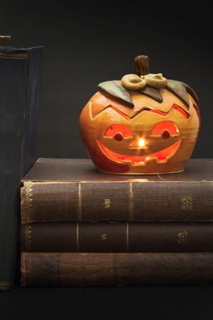 spells: Pumpkin lantern for Halloween and the old witch books. Head carved from a pumpkin on Halloween. Pumpkin tradition. The book of spells, magical book. Textbooks for witches. Stock Photo
