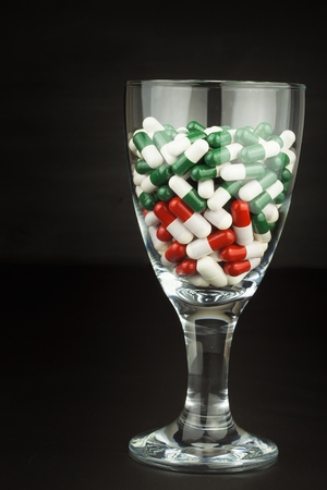 Glass of pills vitamins. Drugs in a glass container on a black background. Nutritional supplements for athletes. Diet concept. Stock Photo