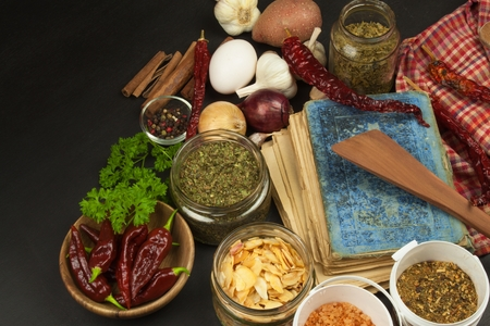 Cookbook and spices on wooden table. Cookbook and ingredients. Garlic, chili peppers and onion. Ingredients for cooking. Home Kitchen. Stock Photo
