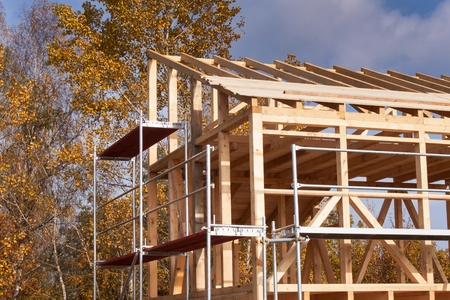 roof framework: Metal scaffolding around the unfinished house. Construction of ecological house. Wooden frame of house under construction.Framed New Construction of a House. Timber house in building process Stock Photo
