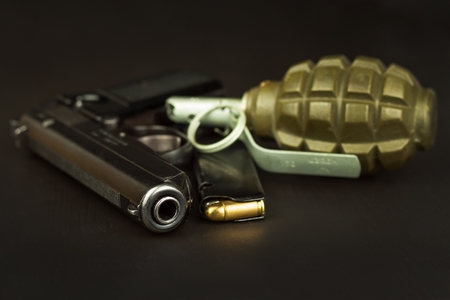Pistol and a grenade on the table  Preparing for battle  Handgun