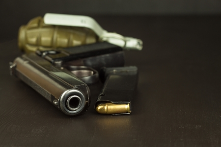 Pistol and a grenade on the table. Preparing for battle. Handgun with ammunition on a dark wooden table. Sales of weapons and ammunition. Advertising on ammunition. New gun and ammunition. Stock Photo