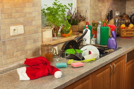 mess: Dirty dishes in the sink after family celebrations. Home cleaning the kitchen. Cluttered dishes in the sink. Housework.