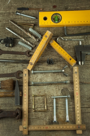 hypothec: Plans to build a house. Rustic wooden background. Tools for builders. Architect designing a house for a young family. House from nails and screws. Needed for building. Ideas about building a house. Stock Photo