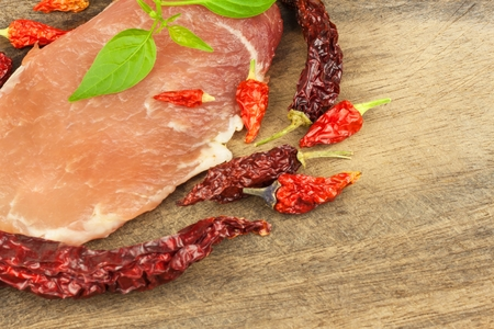 Raw pork on a wooden background. Dried chillies. Preparing spicy food. Spices for cooking meat. Stock Photo