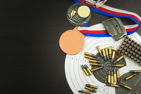 caliber: Concept of shooting Competitions. Sport shooting. Biathlon background diploma. Tools and targets on wooden background. Caliber 22