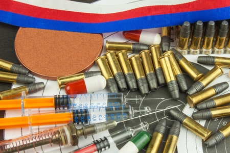 Syringe and medals. Doping in sport shooting. Abuse of anabolic steroids for sports. Deception in biathlon. The International Federation of Biathlon - IBU. Ammunition and winners medals.