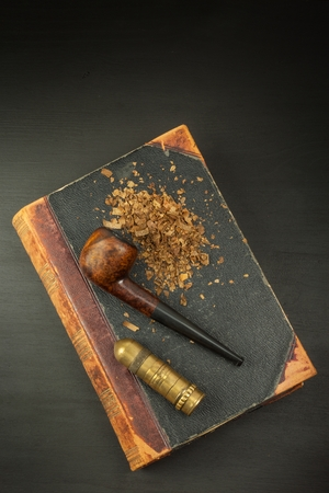 entheogen: Smoking pipe and antique books. Tobacco pipe on ancient books. Relax by reading old books. Tuxedo. Risk of Cancer.