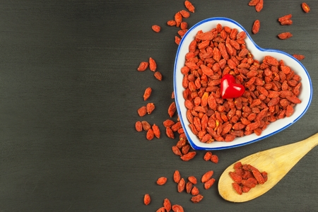 lycium: Goji berries on the wooden table. Traditional Chinese superfood. Healthy diet rich in minerals and vitamins. wolfberry. Lycium chinense Stock Photo