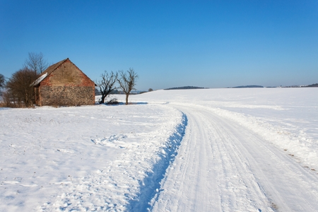 Old abandoned barn in winter. Snow-covered landscape. Rural road in winter. The landscape in the Czech Republic.