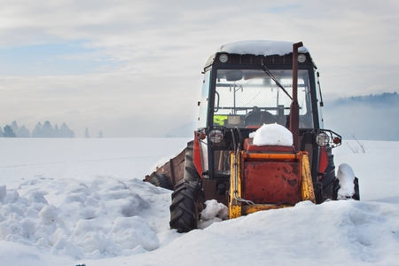 calamity: Old tractor under the snow. Snow calamity in transport. Frozen diesel engine.