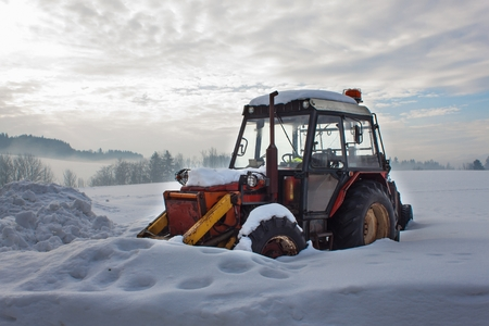 Old tractor under the snow. Snow calamity in transport. Frozen diesel engine.