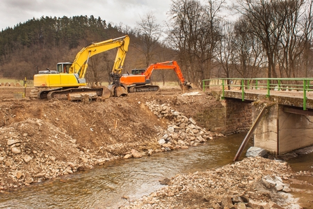 Flood adjustments river. Work on the riverbed. Excavator on the work to strengthen the shoreline of the river