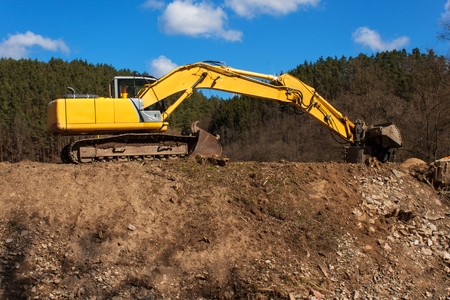Excavator on the work to strengthen the shoreline of the river Stock Photo