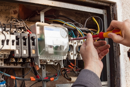replaces: Repair of old electrical switchgear. An electrician replaces old electrical wiring devices Stock Photo