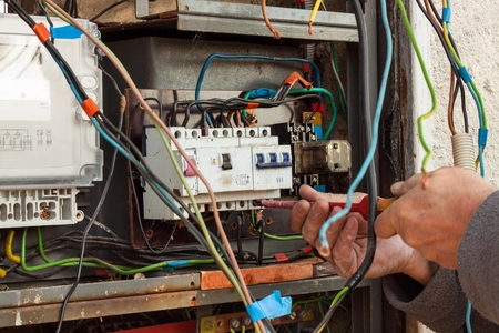 switchgear: Repair of old electrical switchgear. An electrician replaces old electrical wiring devices Stock Photo