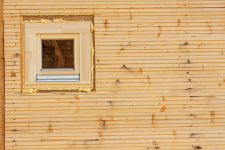 Foam window insulation on wooden construction. Building an eco-house. Heat insulation Stock Photo