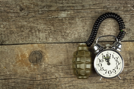 sabotage: Grenade and old alarm clock. Timed bomb. The concept of terrorism Stock Photo