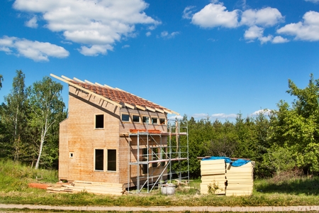 Construction of a wooden roof in an ecological house. External work on the building envelope. The wooden structure of the house near the forest Stock Photo