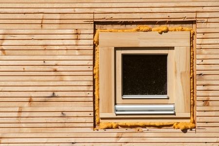 pu foam: Wooden window. Foam window insulation on wooden construction. Building an eco-house. Heat insulation Stock Photo