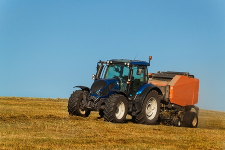 Blue tractor collects dry hay. Agricultural work on the farm in the Czech Republic