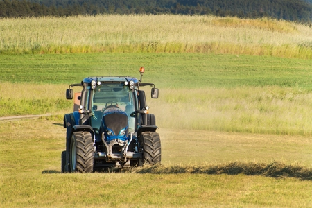 Blue tractor on the pasture.. Agricultural work on the farm in the Czech Republic