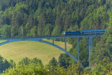 Personal train on a distant bridge over the valley.  The railway bridge in the Czech Republic in the village of Dolni Loucky Stock Photo