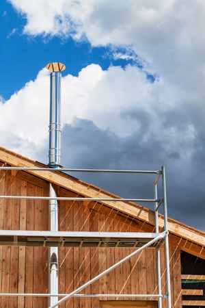 roofing system: Stainless steel chimney on the building of an ecological home. Energy-saving wooden house.  Construction of the cottage near the forest