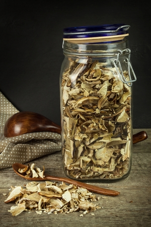 Dried mushrooms in a wooden table. Pile of dried edible mushrooms for sale Imagens