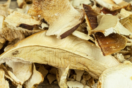 Dried mushrooms in a wooden table. Pile of dried edible mushrooms for sale Stock Photo