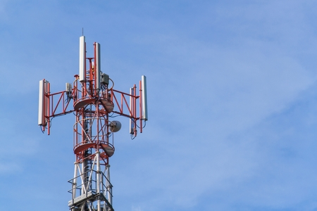 Cell phone and communication towers against blue sky 版權商用圖片